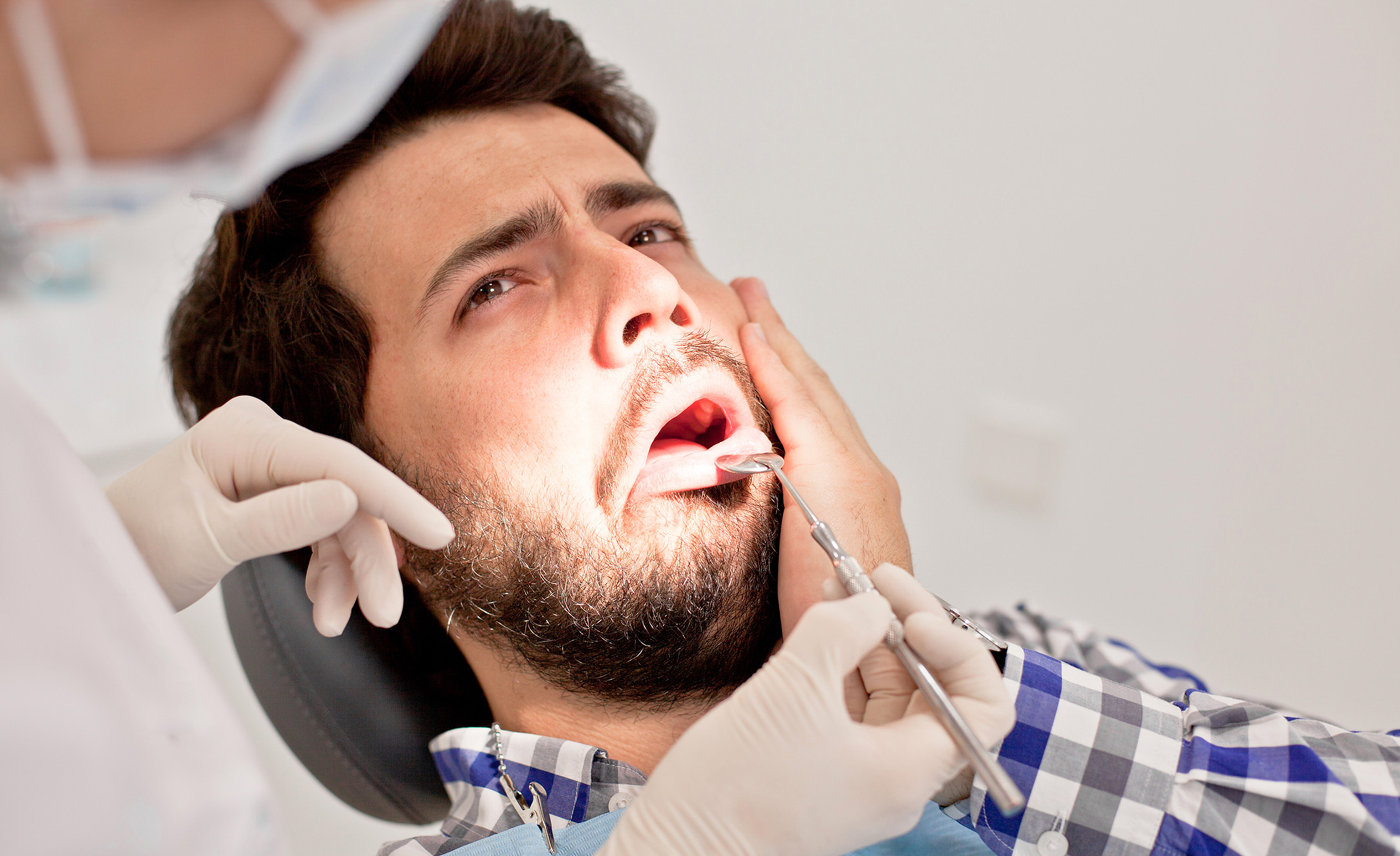 Der Zahnarzt untersucht einen Mann, der sich wegen eines empfindlichen Zahnes den Kopf greift.