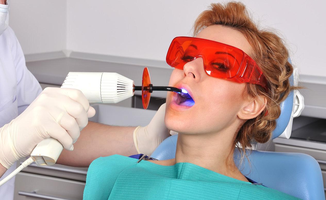 Eine Frau mit roten Haaren sitzt in einem Zahnarztstuhl während der Zahnfüllung.