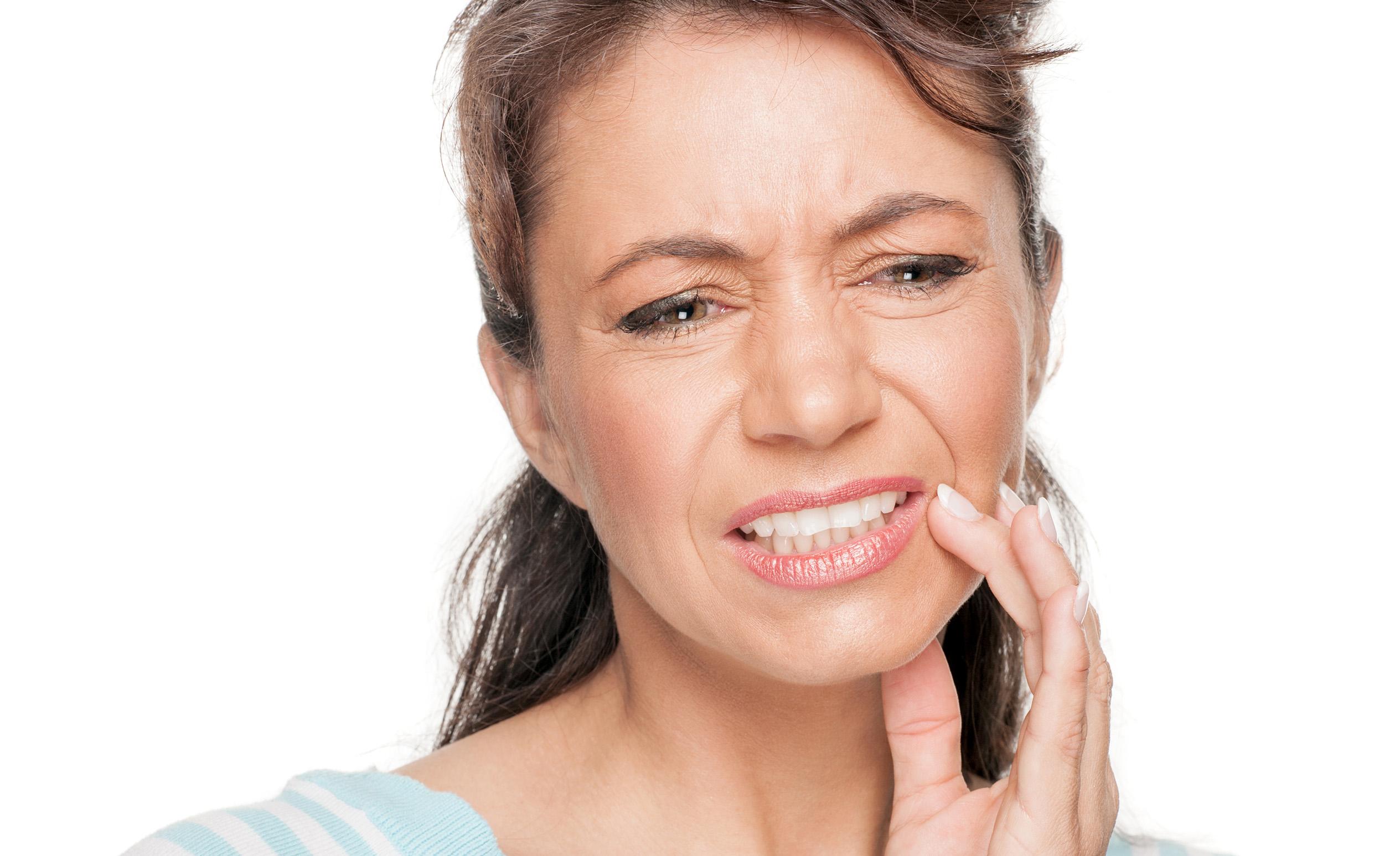 Eine Frau hält sich die Hand auf dem Gesicht, weil ihr der Zahn sehr schmerzt.
