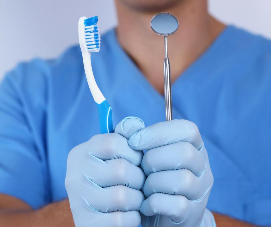 Dr. Varajti Artúr fogorvos, szájsebész bal kezében egy fogászati tükröt, jobb kezében pedig egy fogkefét tart.