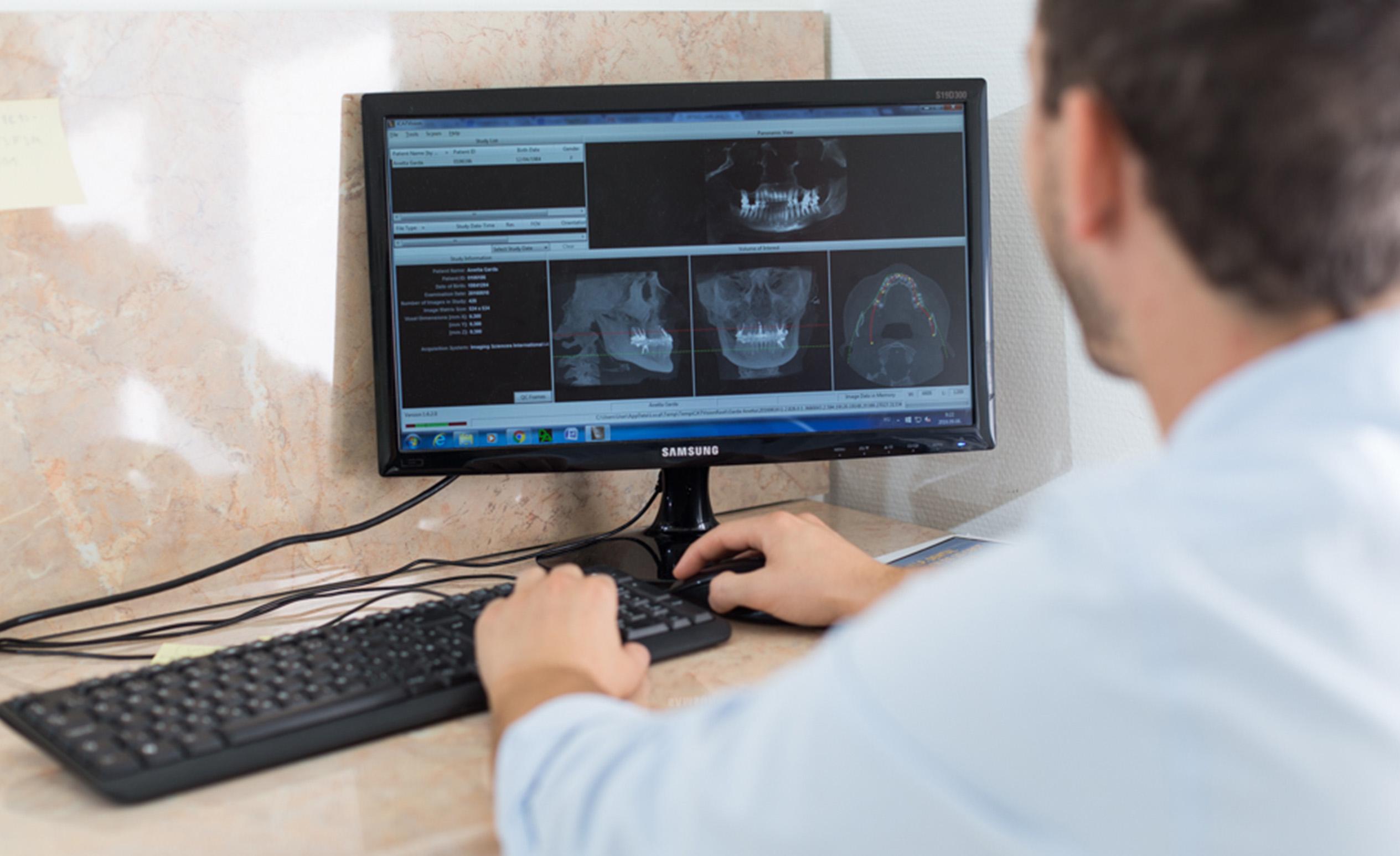 Ein Budapester Zahnarzt sitzt vor dem Computer, er gebraucht ein Programm zur Unterstützung der Zahnimplantation.