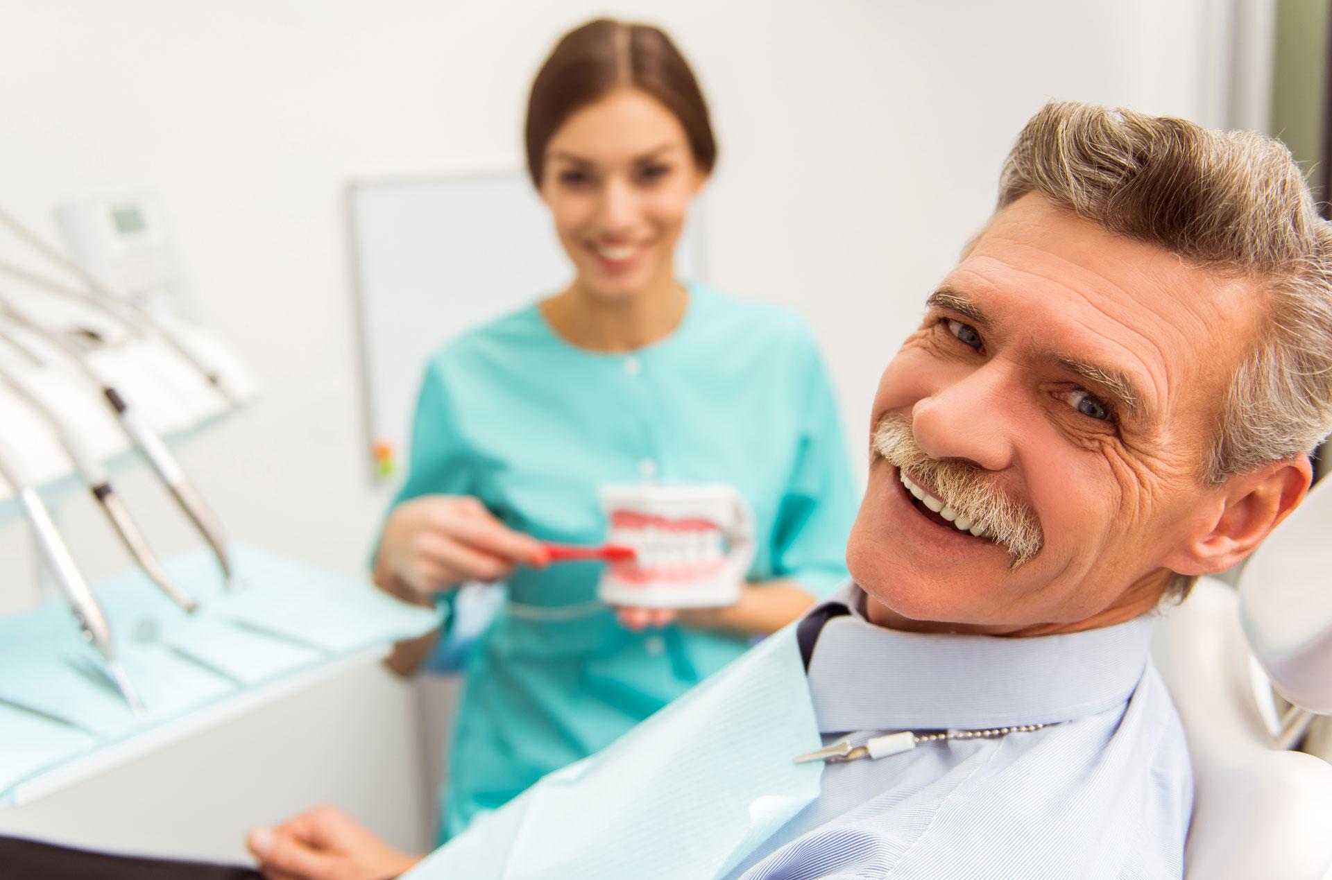 Fog implantátum beültetés után mosolyog egy idősebb férfi egy fogorvosi székben.