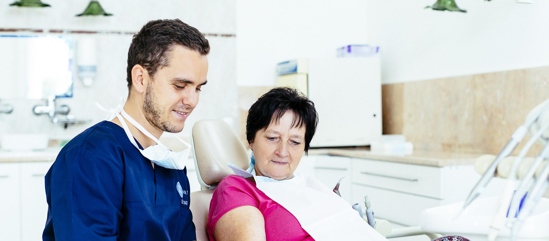 Vor der Beseitigung der Wurzelspitze konsultiert der Kieferchirurg mit dem Patienten im Budapester zahnärztlichen Sprechzimmer.