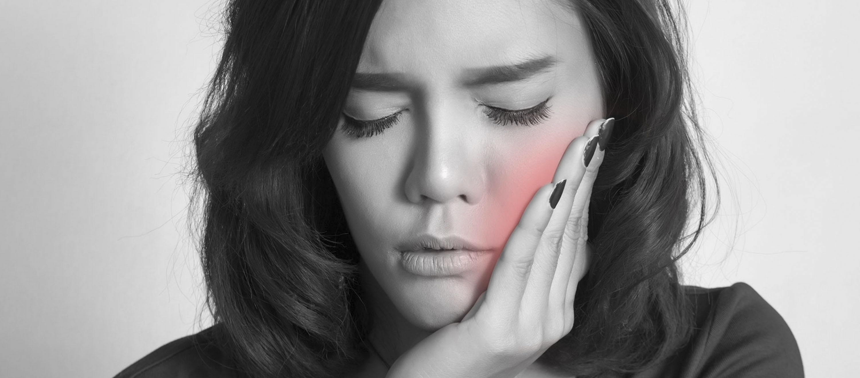 Der Weisheitszahn tut ihr weh, eine hübsche junge Frau leidet an Schmerzen.