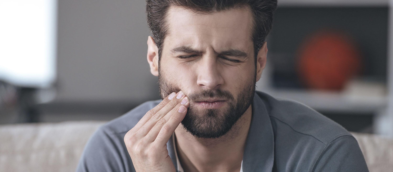 Der Mann hat Zahnschmerzen, weil eine Zyste im Zahn ist.