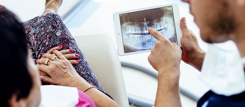 Der Zahnarzt und die Patientin sprechen über die Möglichkeiten und Arten des Zahnersatzes.