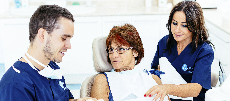 Der Zahnarzt und die Patientin sprechen mit einander vor der Zahnimplantation. Die Patientin wird einen festen Zahnersatz bekommen.