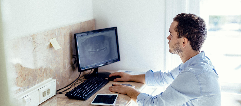 Der Kieferchirurg schaut das Monitor vor der Knochenergänzung in der Budapester Zahnklinik.